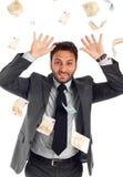 Lycklig man som tycker om regna av pengar arkivfoto