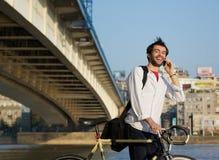 Lycklig man som utomhus går med cykeln och mobiltelefonen Arkivbilder