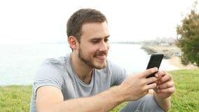 Lycklig man som utomhus smsar på telefonen arkivfilmer