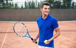 Lycklig man som utomhus spelar i tennis Royaltyfri Bild