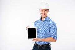 Lycklig manarkitekt i byggnadshjälmen som rymmer minnestavlan för tom skärm Royaltyfri Fotografi