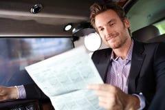 Lycklig manavläsningsnyheterna i lyxig bil fotografering för bildbyråer