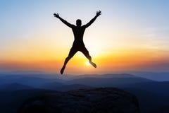 Lycklig manbanhoppning för glädje på maximumet av berget, klippa på solnedgången Framgång vinnare, lycka arkivfoto