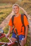 Lycklig mancyklist som sitter på vägen Royaltyfri Fotografi