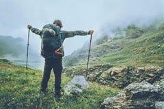 Lycklig manfotvandrare som fotvandrar i dimmiga berg fotografering för bildbyråer