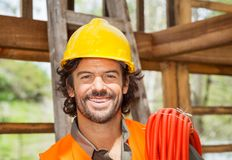 Lycklig manlig arbetare med röret på konstruktionsplatsen fotografering för bildbyråer