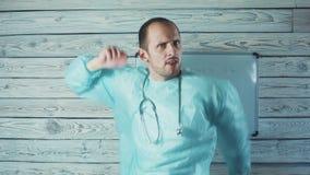 Lycklig manlig Caucasian doktor med ljus skäggdans i hans medicinska kontor lager videofilmer