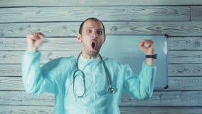 Lycklig manlig Caucasian doktor med ljus skäggdans i hans medicinska kontor arkivfilmer