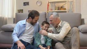 Lycklig manlig familj som skrattar uppriktigt att meddela i vardagsrum, utveckling arkivfilmer