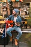 Lycklig manlig gitarrist som spelar sång nära stång royaltyfri fotografi