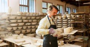 Lycklig manlig keramiker som rymmer keramiska koppar i magasinet 4k stock video