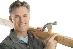 Lycklig manlig snickareHolding Hammer And planka Arkivbild
