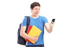 Lycklig manlig student som ser i hans mobiltelefon Royaltyfria Foton