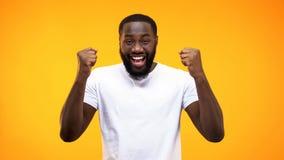 Lycklig manlig vinnare i den vita t-skjortan som visar framgånggesten, prestationtecken arkivbild