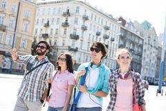 Lycklig manvisning något till manliga och kvinnliga vänner på stadsgatan arkivfoto