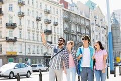 Lycklig manvisning något till vänner på stadsgatan fotografering för bildbyråer