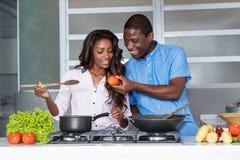 Lycklig matlagning för afrikansk amerikanförälskelsepar på kök fotografering för bildbyråer