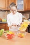 Lycklig matlagning för tonårs- flicka på hennes egna Arkivbild