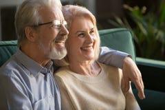 Lycklig medelålders familj, fru och make som hemma omfamnar royaltyfri foto