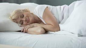 Lycklig medelålders kvinnlig som sover i säng på den ortopediska madrassen, hälsa lager videofilmer