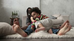 Lycklig mellan skilda raser familj som barfota sitter på golv stock video