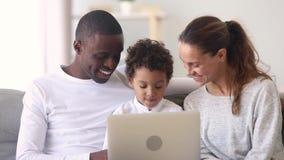 Lycklig mellan skilda raser familjmammafarsa och liten sonbruksbärbar dator stock video