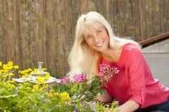 Lycklig mellersta ålderkvinna med blommor i henne som är trädgårds- arkivbilder