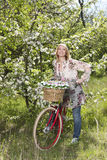 Lycklig mellersta ålderkvinna med cykeln royaltyfri bild