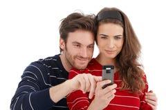 lycklig mobil telefon för par som ler genom att använda Arkivbild