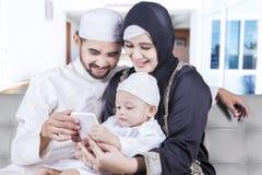 Lycklig mobiltelefon för muslimfamiljbruk hemma Royaltyfria Foton