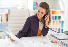 Lycklig modeformgivare i regeringsställning som talar telefonen arkivfoto