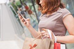 Lycklig modekvinna med påsen genom att använda mobiltelefonen, köpcentrum Arkivbilder