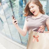 Lycklig modekvinna med påsen genom att använda mobiltelefonen, köpcentrum Royaltyfri Fotografi