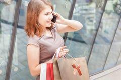 Lycklig modekvinna med påsen genom att använda mobiltelefonen, köpcentrum Arkivbild