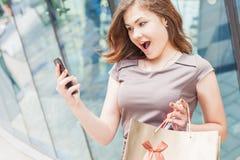 Lycklig modekvinna med påsen genom att använda mobiltelefonen, köpcentrum Royaltyfri Foto