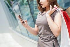Lycklig modekvinna med påsen genom att använda mobiltelefonen, köpcentrum Arkivfoton