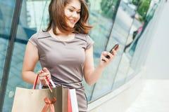 Lycklig modekvinna med påsen genom att använda mobiltelefonen, köpcentrum Fotografering för Bildbyråer