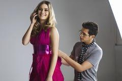 Lycklig modell genom att använda mobiltelefonen medan manlig formgivare som justerar hennes klänning i studio Royaltyfri Foto