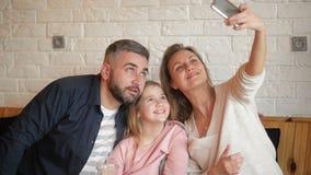 Lycklig moder, fader And Little Girl som har gyckel och tar Selfie vid Smartphone på kafét arkivfilmer