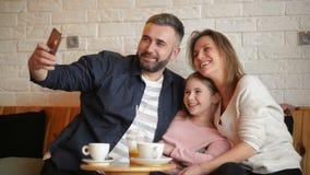 Lycklig moder, fader And Little Girl som har gyckel och tar Selfie vid Smartphone p? kaf?t lager videofilmer