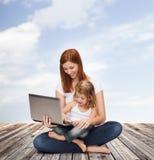 Lycklig moder med den förtjusande lilla flickan och bärbara datorn Royaltyfria Bilder