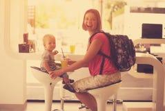 Lycklig moder med ett barn i ett kafé Arkivbild