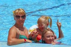 Lycklig moder med hennes döttrar som sitter i simbassängen som framme poserar av kamera royaltyfri bild