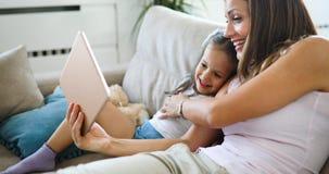 Lycklig moder med hennes dotter som använder den digitala minnestavlan royaltyfria foton