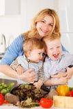 Lycklig moder med hennes söner i köket Royaltyfri Bild
