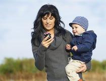 Lycklig moder med pysen på mobiltelefon Royaltyfria Foton