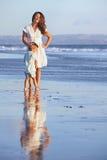 Lycklig moder med sonen som blir på den släta havsstranden Arkivbilder