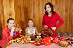 Lycklig moder med tonåringdottern som äter pannkakan arkivfoto