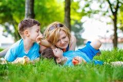 Lycklig moder med ungar arkivbild