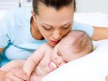 lycklig moder nära nyfött sova barn Arkivbilder